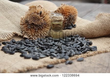 Dry flower sunflower jar of oil and seeds on sacking wooden boards