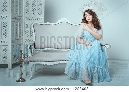 Overweight women sitting on a sofa in the room.
