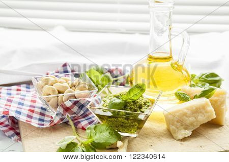 Basil pesto fresh basil leaves parmigiano cheese olive oil and cashew seeds on light wooden background