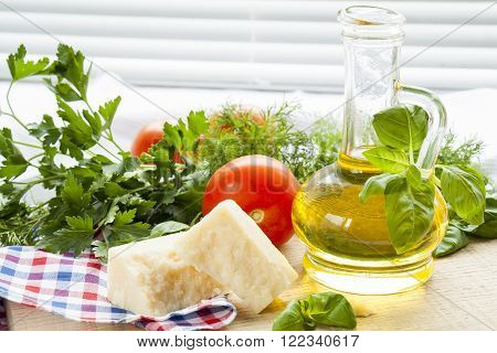 Parmigiano cheese, olive oil herbs and tomatoes on wooden background