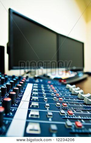 Audio-Mixer mit Computer im Hintergrund - geringe Schärfentiefe