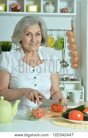 Senior woman with grey hair cooking in kitchen