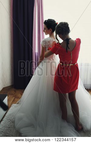 Bridesmaids Help Put On & Tie Corset On Bride's Wedding Dress