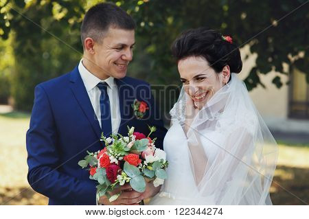 Happy, Cheerful Newlywed Couple Laughing In Park With Bouquet