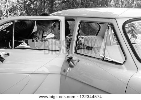 Beautiful Brunette Bride In Retro White Car Kissing Handsome Groom B&w