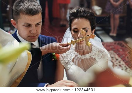 Spiritual Beautiful Bride And Groom Taking Vows In Churchm Kissing Crucifix