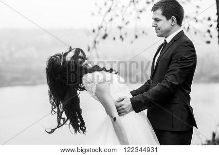 Happy Beautiful Couple Of Newlyweds Hugging Near Romantic Lake B&w