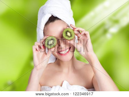 Smiling young woman holing a kiwi in front of her eyes