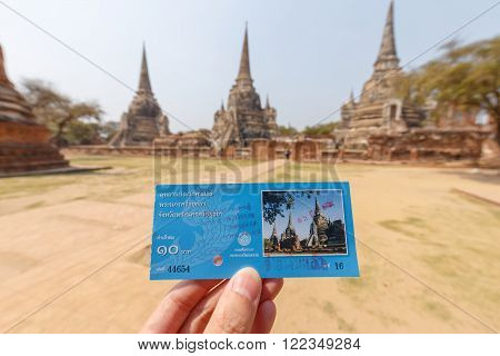 Ayutthaya Thailand - March 16 2016: Hand held the tour ticket of ancient park called Wat Prasri Sanpetch in Ayutthaya Thailand. The blurred background was tourists walking around temple area.