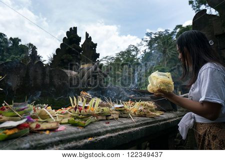 UBUD, BALI - MARCH 14, 2016: A Balinese Hindu devotee prays at the altar in a ritual ceremony at the Pura Tirta Empul (temple), Bali. Hinduism is the religion of the original Balinese inhabitants.
