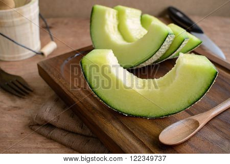 Juicy slice melon on rustic wooden table background.
