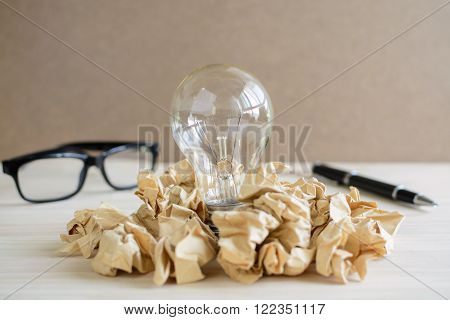Crumpled paper balls with eye glasses and pen on wooden desk creative writing concept