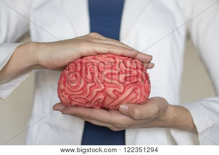 woman hands holding a brain as a protection gesture