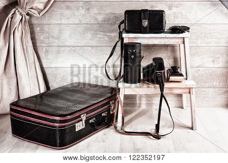 Vintage black leather suitcase trunks for lenses camera eyeglasses and paperweight on the shelf in the corner of the wooden room.