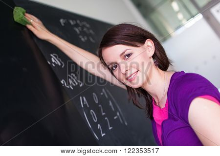 Pretty, young college student writing on the chalkboard/blackboard during a math class