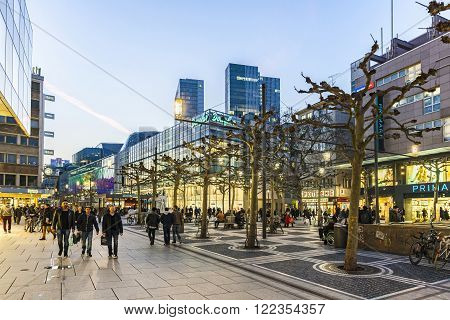 FRANKFURT, GERMANY - MAR 18, 2016: people walk along the Zeil in the evening in Frankfurt. The Zeil is since changing to pedestrian zone in 1970 Germanys most popular pedestrian Zone.