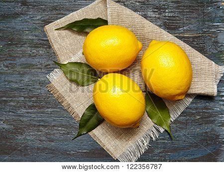 Fresh lemons with leaves . On a linen napkin . Dark background