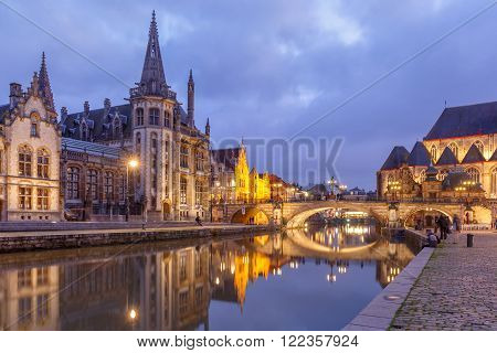 Picturesque medieval building and St Michael's Bridge on the quay Graslei in Leie river at Ghent town in the evening, Belgium