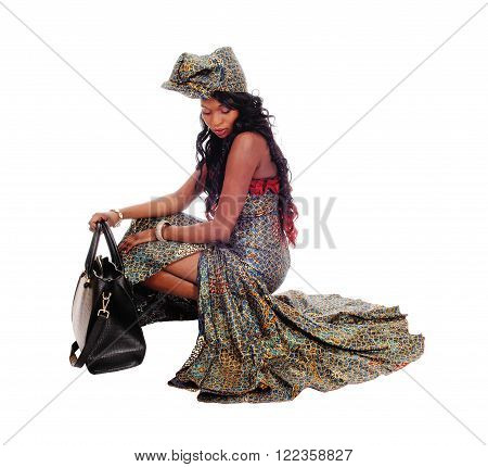 A beautiful African American woman crouching in an African long dress