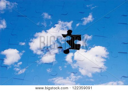 Blue sky with clouds as a puzzle (with a black hole instead of one piece)