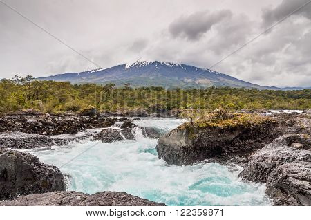 The Petrohue Falls and Osorno Volcano with its snow peak in Puerto Varas in cloudy weather south of Chile.