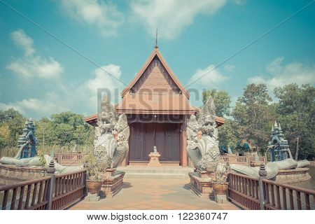Pathum Thani Thailand - April 18 2015 : Wat Phakhlong 11 is a temple has a wooden temple in the middle of the water. Surrounded by a large naga statue at Nong Suea District Pathum Thani.