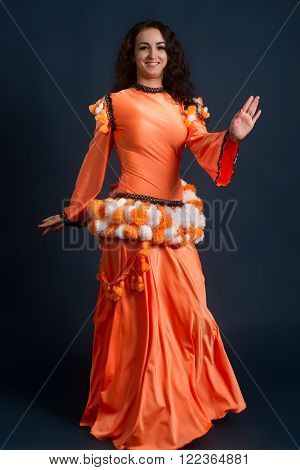beauty dancer posing in traditional orange costume against a dark background