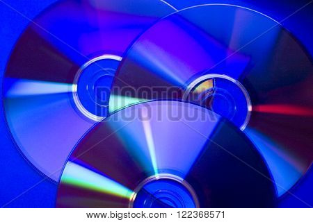 Slightly blurred compact discs in dark blue tones (as an abstract technological background)