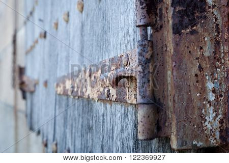 Details of an old rusty hinge on wooden shutters.