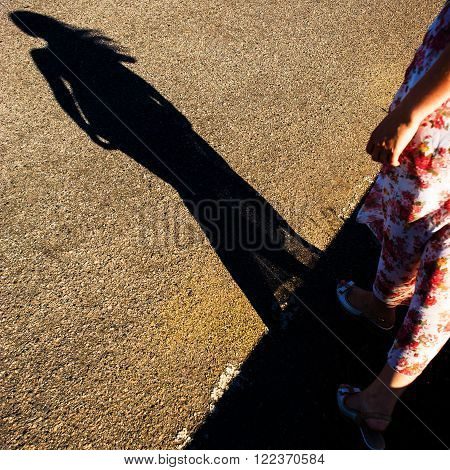 Shadow of a female figure on the asphalt road