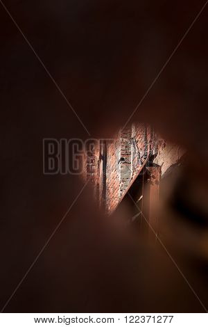 A small hole provides a space to peek through into an old, abandoned, military structure in decay.
