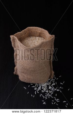 Bag of rice on black background. Old style. With several white rie grains outside.