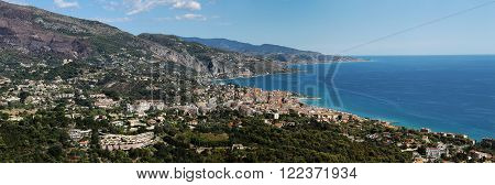 Monte Carlo Monaco - September 20 2015: panoramic view of picturesque resort town on sea side below hillsides mountains against bright blue sky on seascape background horizontal picture