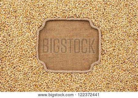 Figured frame made of rope with barley grains on sackcloth with place for your creativity