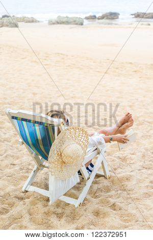 Woman sitting on a deck chair relaxing at the tropical beach