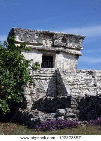A Mayan temple at the archeological site of Tulum surrounded by flowers in the Yucatán Peninsula of Mexico.