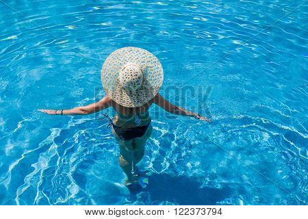 Woman with hat  standing in the swimming pool