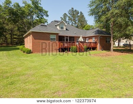 Back of residential house with wooden deck and landscaping