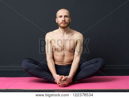 Sport and fitness. Young man with naked torso is performing groin muscle stretching - butterfly exercise on the mat, gray background** Note: Visible grain at 100%, best at smaller sizes
