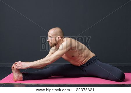Sport and fitness. Young man with naked torso is doing tilt to the toes on the mat** Note: Visible grain at 100%, best at smaller sizes