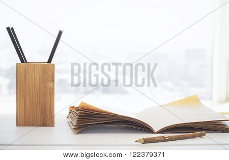 Wooden penpot and copybook on light background