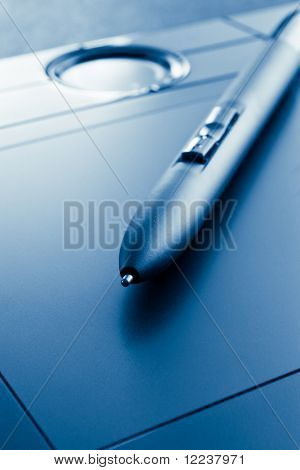 closeup of graphic tablet  with pen blue tinted