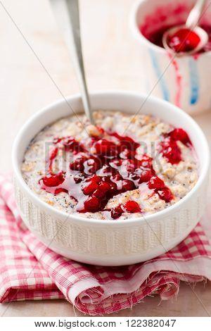 porridge with cranberry sauce in a bowl . selective focus