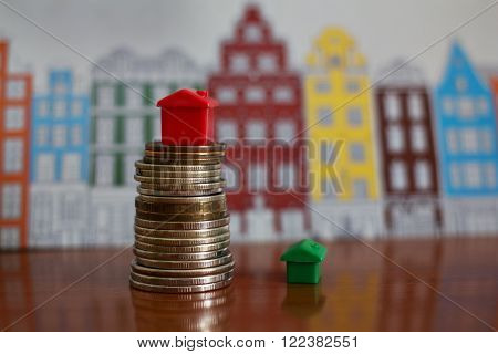 Small plastic house model on top of stacked coins.