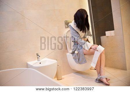 Brunette Woman Sitting On Toilet In The Bathroom.