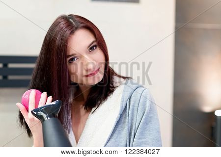 Brunette woman brushing and drying her hair in the bathroom. Wears a grey dressing-gown