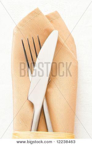 knife and fork on beige napkin