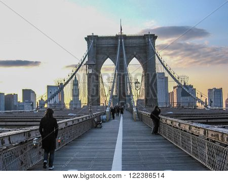 Brooklyn, New York, United States - 30th April, 2008: people walk on the famous Brooklyn Bridge at sunset.