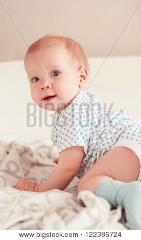 Smiling baby boy crawling in bed. Posing in room. Bedtime. Cute baby child. Childhood.