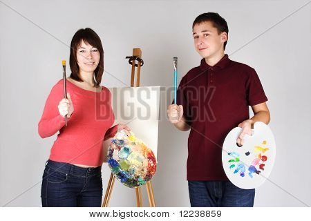 Young Man And Girl Standing Near Easel, Holding Brushes With Palettes And Smiling